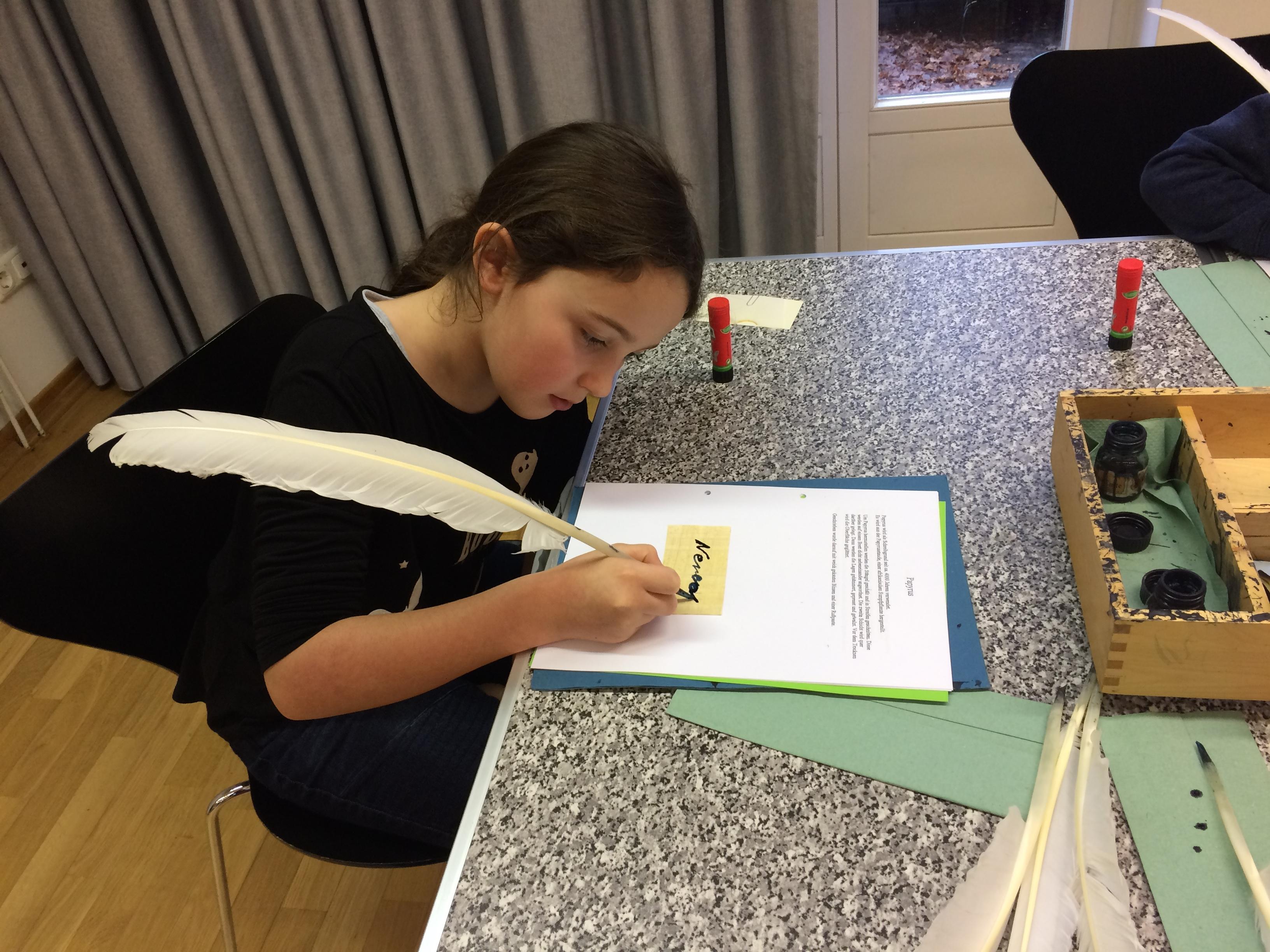Nerea übt das Schreiben mit der Gänsefeder.